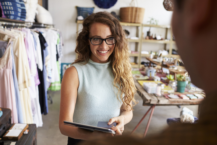 Female boutique manager greeting client in shop
